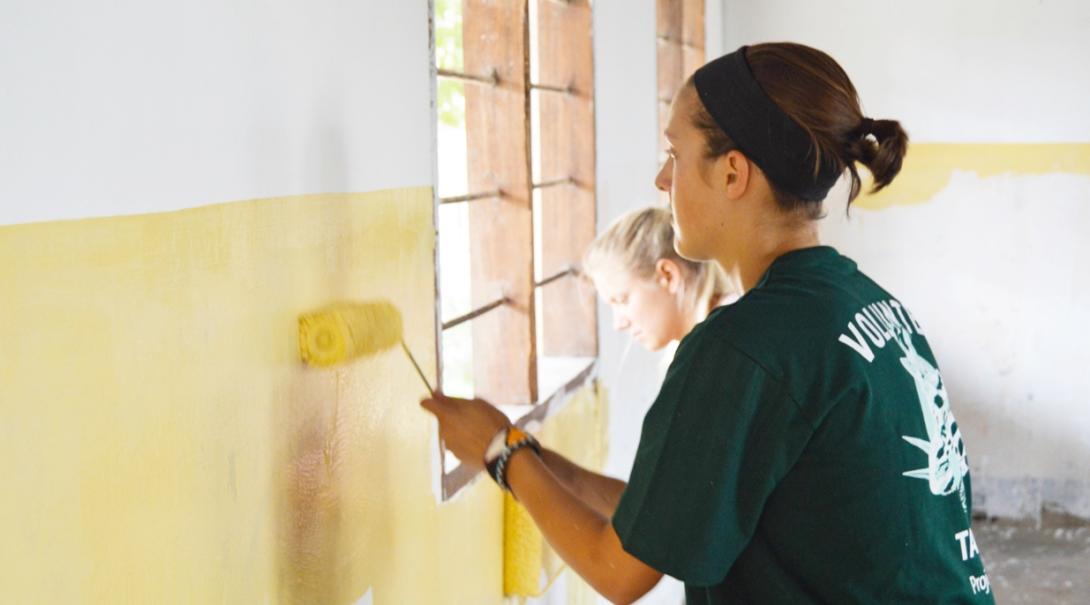 タンザニアの学校の壁のペインティングに励む建築ボランティア